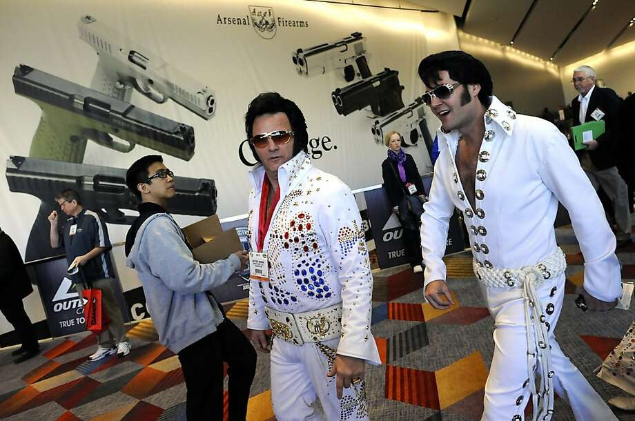 Elvis impersonators walk past a large banner for Arsenal Firearms in the lobby of the convention center.  SHOT Show, the world's largest gun show, opened at the Sands Convention Center in Las Vegas, NV on Tuesday January 15th, 2013, where an estimated 60,000 industry enthusiasts are expected to attend. Photo: Michael Short, Special To The Chronicle