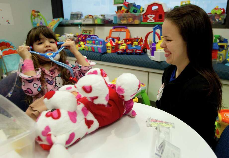 Meara Biggerstaff, 4, left, plays with a toy stethoscope with Child Life Specialist Kari Lown at Texas Children's Hospital Wednesday, Jan. 9, 2013, in Houston. Child Life specialists use play and other techniques to help reduce stress and anxiety for children undergoing medical procedures. Photo: Brett Coomer, Houston Chronicle / © 2013 Houston Chronicle