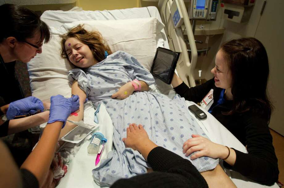 Child life specialist Kari Lown distracts Julia Cuevas, 15, with music as Dr. Lindsay Burrage does a biopsy at Texas Children's Hospital. Play and other techniques reduce anxiety for children during medical procedures. Photo: Brett Coomer, Houston Chronicle / © 2013 Houston Chronicle