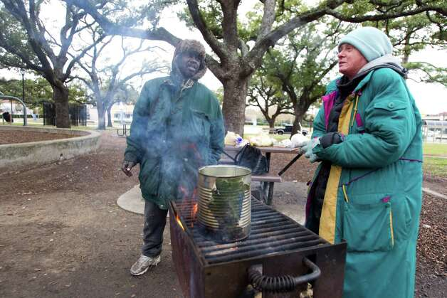 James Adams, left, and Diana Tyrrell stand around a fire built in a barbecue grill trying to stay warm at Peggy Park Tuesday, Jan. 15, 2013, in Houston. Temperatures hovered near 40 degrees on Tuesday, with an expected low of 35 during the night. Photo: Brett Coomer, Houston Chronicle / © 2013 Houston Chronicle