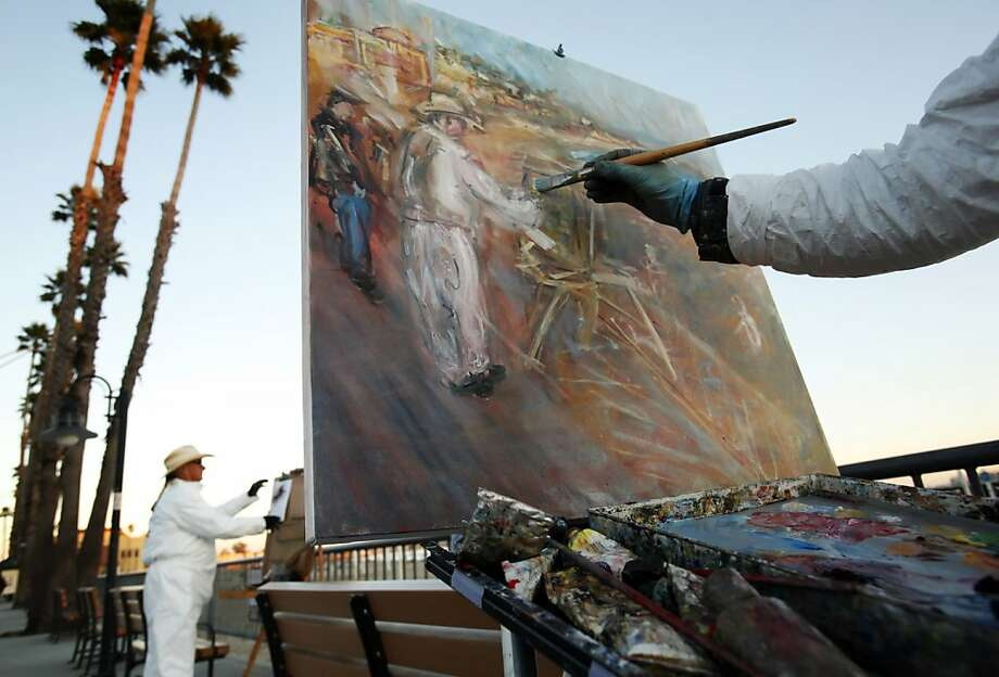 Andrew Purchin, painting artist Jon Bailiff (left), on Beach Street in Santa Cruz, organized an art-making installation for Monday's inauguration. Photo: Carlos Avila Gonzalez, The Chronicle
