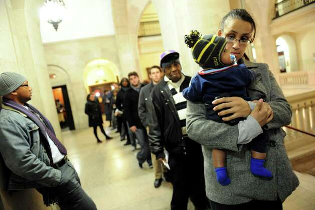 Tiana Taylor, right, and her 5-month-old baby, Lucian Lee, wait in line for a resident parking permit on Tuesday, Jan. 15, 2013, at City Hall in Albany, N.Y. Taylor, who lives in the Mansion neighborhood, said she already noticed more open parking spots on her street. (Cindy Schultz / Times Union) Photo: Cindy Schultz / 00020764A