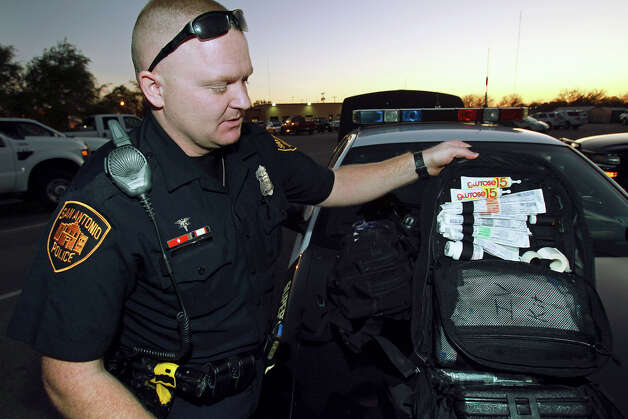 SAPD patrolman Justin Remmers, a Tac Med, checks over his medical equipment as he  works his shift on the East Side on December 18, 2012. Photo: Tom Reel, San Antonio Express-News / ©2012 San Antono Express-News