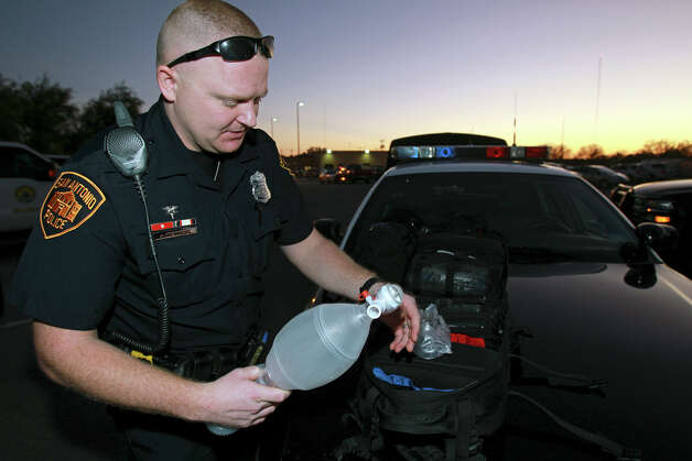 SAPD patrolman Justin Remmers, a Tac Med, checks out his medical equipment as he  works his shift on the East Side on December 18, 2012. Photo: Tom Reel, San Antonio Express-News / ©2012 San Antono Express-News