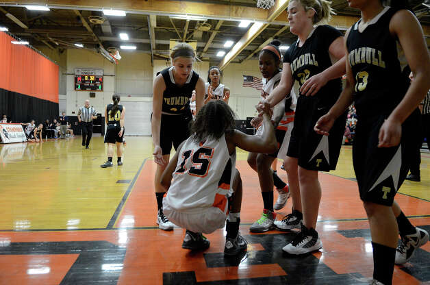 Trumbull players offer a helping hand to Stamford #15 Ansia Fortt as Stamford High School hosts Trumbull High School in girls varsity basketball in Stamford, CT on Jan. 15, 2013. Photo: Shelley Cryan / Shelley Cryan for the Stamford Advocate/ freelance Shelley Cryan