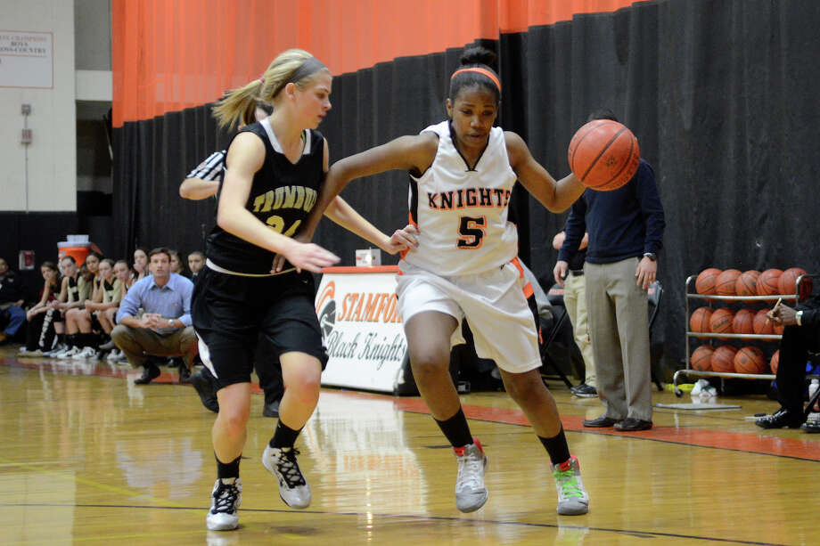 Stamford #5 Ashyla Cody gains some ground, defended by Trumbull #24 Amanda Pfohl as Stamford High School hosts Trumbull High School in girls varsity basketball in Stamford, CT on Jan. 15, 2013. Photo: Shelley Cryan / Shelley Cryan for the Stamford Advocate/ freelance Shelley Cryan