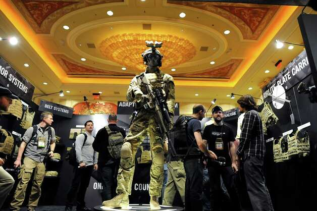 Conventioners browse through the booth of military performance gear maker Crye Percision of Brooklyn, NY.  SHOT Show, the world's largest gun show, opened at the Sands Convention Center in Las Vegas, NV on Tuesday January 15th, 2013, where an estimated 60,000 industry enthusiasts are expected to attend. Photo: Michael Short, Special To The Chronicle / ONLINE_YES