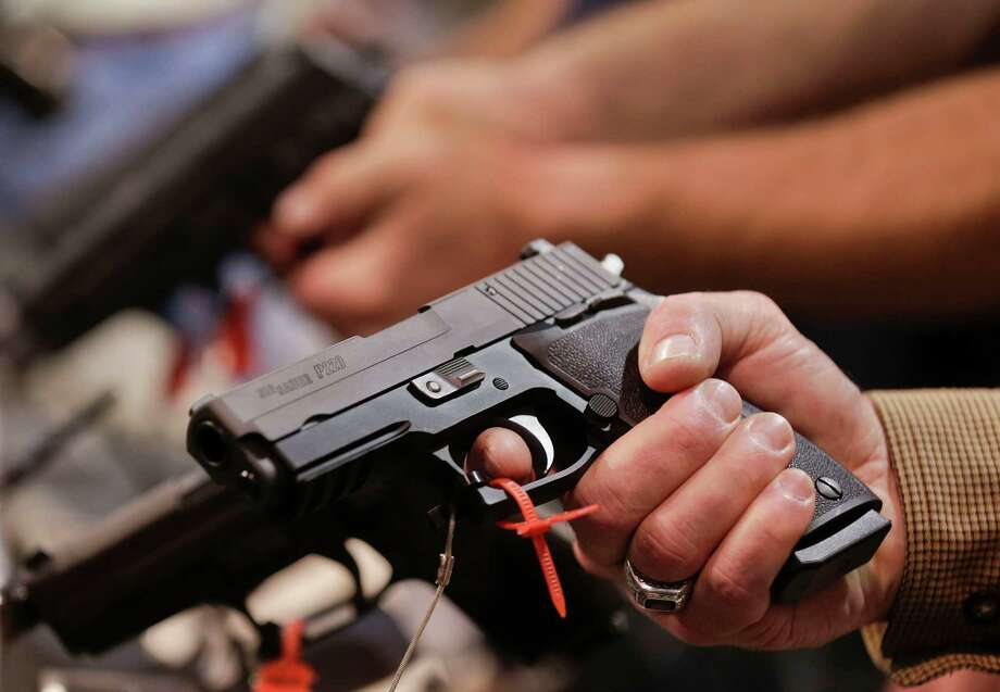 A convention attendee handles a Sig Sauer P220 .45 caliber semiautomatic pistol at the 35th annual SHOT Show, Tuesday, Jan. 15, 2013, in Las Vegas. The National Shooting Sports Foundation was focusing its trade show on products and services new to what it calls a $4.1 billion industry, with a nod to a raging national debate over assault weapons. Photo: Julie Jacobson, (AP Photo/Julie Jacobson) / Associated Press