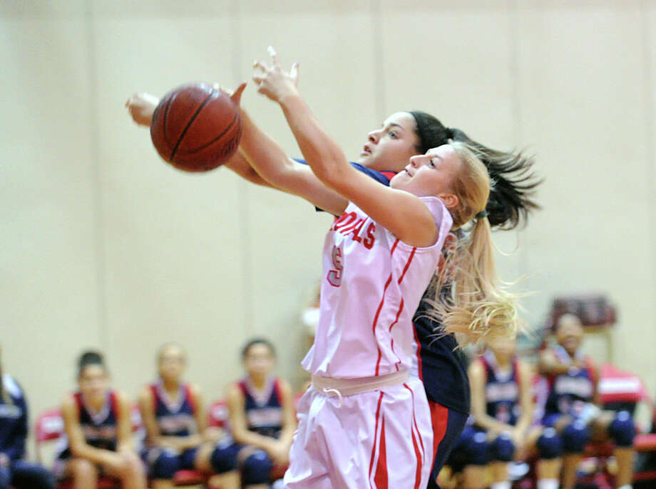 Foreground, Rebecca DeCarlo of Greenwich goes for an offensive rebound against Sabrina Rodriquez of Brien McMahon during the girls high school basketball game between Brien McMahon High School and Greenwich High School at Greenwich, Tuesday night, Jan. 15, 2013. Photo: Bob Luckey / Greenwich Time