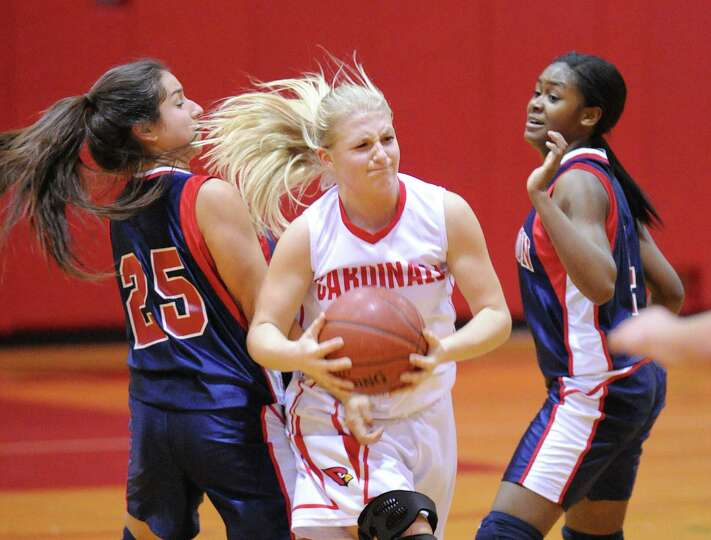 At center, Rebecca DeCarlo of Greenwich splits Brien McMahon defenders, Natalie Leslie, # 25, left,