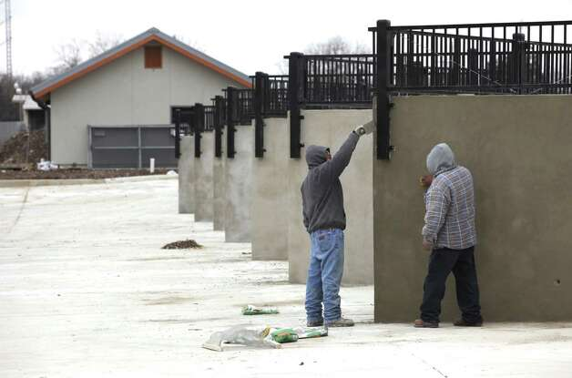 Construction workers smooth out the walls at the new bulky waste drop off location on Frio City Rd. The city of San Antonio will open its new bulky drop-off location, on Friday, at its Bitters brush recycling center in an attempt to curb prolific illegal dumping.  The Frio City Rd. location will be open later this year.  Tuesday, Jan. 15, 2013. Photo: Bob Owen, San Antonio Express-News / ©2013 San Antonio Express-News