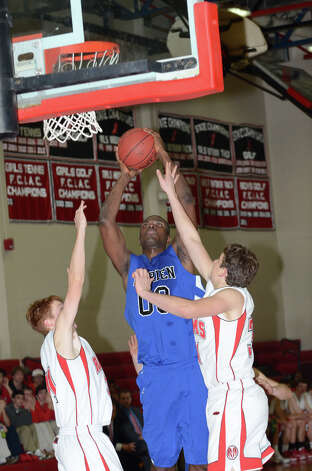 Darien's Chima Azuonwu (0) goes up for a shot as New Canaan's Andrew Penchuck (31) and Zachary Allen (34) defend during the boys basketball at New Canaan High School on Tuesday, Jan. 15, 2013. Photo: Amy Mortensen / Connecticut Post Freelance