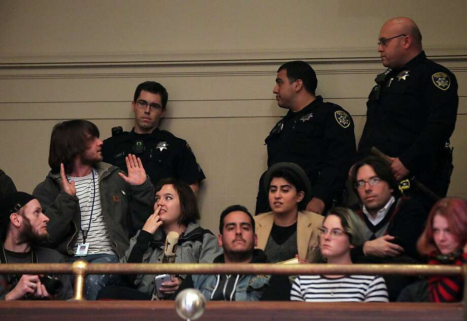 "An unidentified protestor is confronted by Oakland Police who were called to quit the gallery Tuesday Jan 15, 2013. The Oakland City Council's Public Safety Committee meeting Tuesday heard from hundreds of it's citizens that wanted to voice their opinions about consultant William Bratton, ""stop and frisk "" policy in Oakland California. Photo: Lance Iversen, The Chronicle"