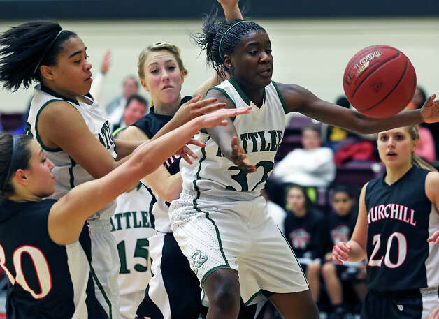 Reagan's Moriah Mack (center) reaches for a rebound during the Rattlers' 54-37 victory over Churchill. Mack scored a game-high 17 points as Reagan avenged an earlier loss to the Chargers. Photo: Tom Reel, San Antonio Express-News / ©2012 San Antono Express-News