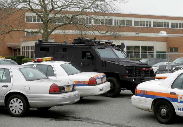 A heavily armored vehicle drives in front of Elmont Memorial High School during a lockdown in Elmont, N.Y., Tuesday, Jan. 15, 2013.  The Long Island school is returning to normal after a report of a gun prompted an hours-long lockdown. (AP Photo/Seth Wenig) Photo: Seth Wenig
