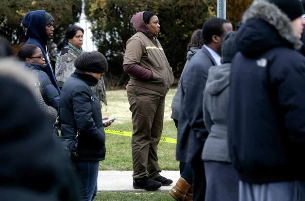 Parents and family members wait across the street from Elmont Memorial High School for information about the lockdown and to pick up their children in Elmont, N.Y., Tuesday, Jan. 15, 2013.  The Long Island school is returning to normal after a report of a gun prompted an hours-long lockdown. (AP Photo/Seth Wenig) Photo: Seth Wenig