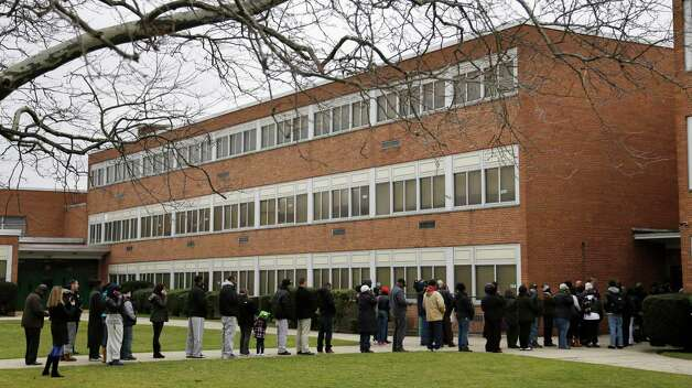 Family members wait in line to pick up students after a lockdown was lifted at Elmont Memorial High School in Elmont, N.Y., Tuesday, Jan. 15, 2013.  The Long Island school is returning to normal after a report of a gun prompted an hours-long lockdown. (AP Photo/Seth Wenig) Photo: Seth Wenig