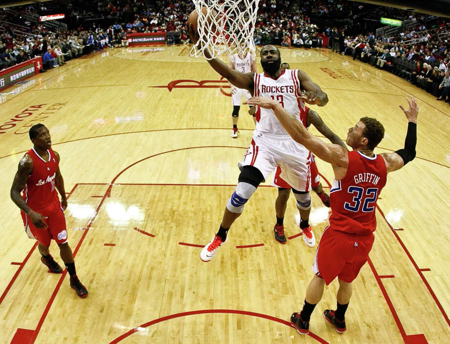 Rockets guard James Harden drives past Clippers forward Blake Griffin in the first quarter. Photo: Nick De La Torre / © 2013  Houston Chronicle