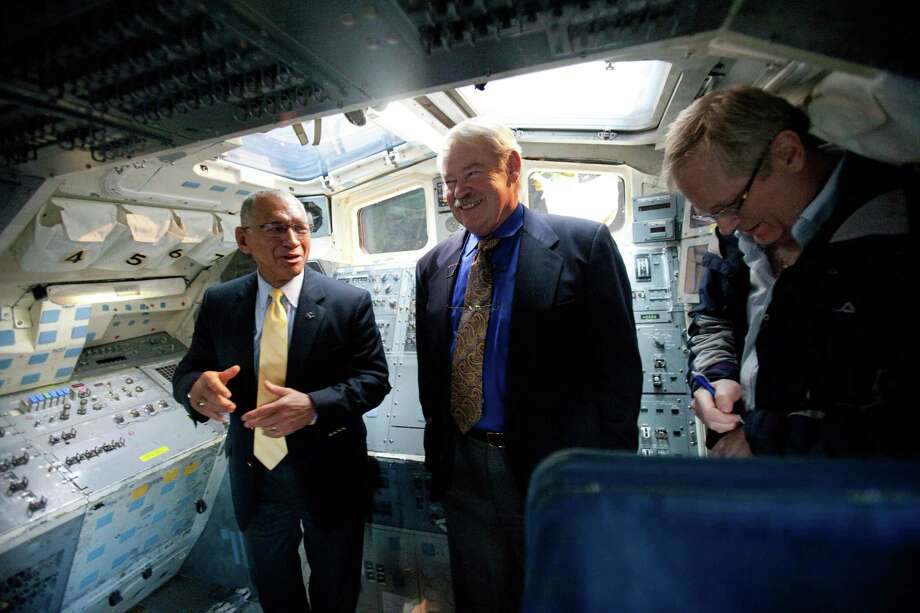 NASA Administrator Charles Bolden, left, tells stories of his own time training in the Space Shuttle's Full Fuselage Trainer with former NASA