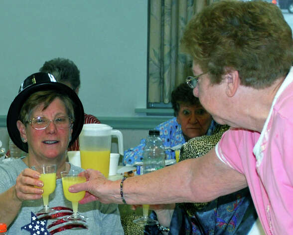 Marie Crawford, left, and Pat Hammer make a toast to 2013 with virgin mimosas during the New Yearís pajama party held Jan. 4, 2013, at the New Milford Senior Center. Photo: Deborah Rose