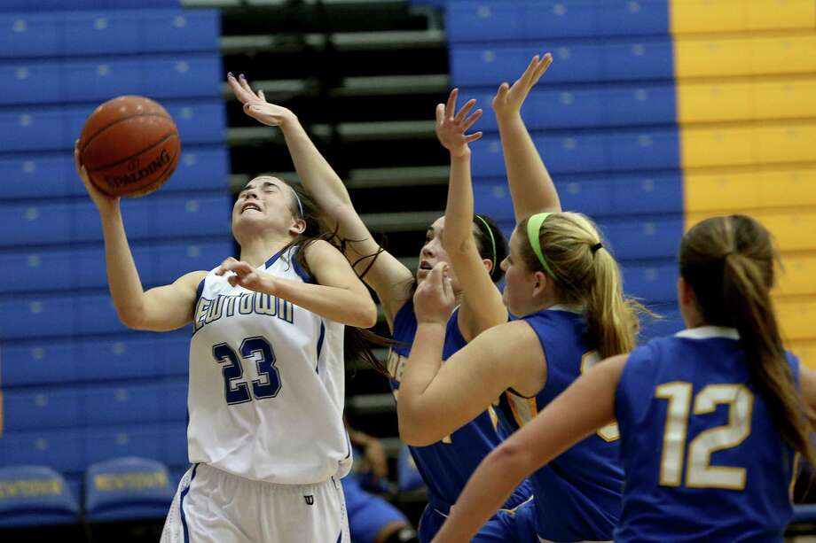 Mike Ross Connecticut Post freelance -Newtown High School's #23 Bridget Powers goes to the basket and scores against Brookfield's # 34 Stephanie Hunt #24 Paulina Hurron during first half action on Tuesday evening. Photo: Mike Ross / www.mikerossphoto.com