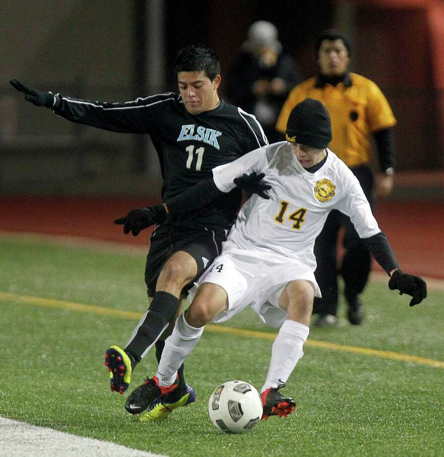 Elsik's Oscar Acosta (11) battles for the ball with Klein Oak's Sergio Santamaria (14) as Elsik High School defeated Klein Oak 2-1 at Butch Theiss Field at Klein Tuesday, Jan. 15, 2013, in Houston. Photo: Johnny Hanson, Houston Chronicle / © 2013  Houston Chronicle