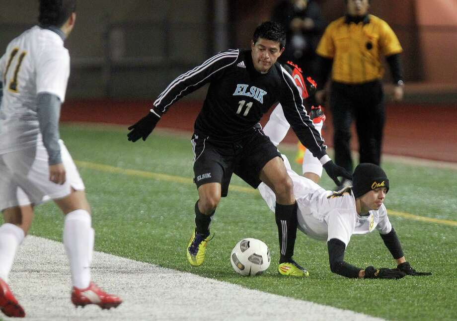 Elsik's Oscar Acosta (11) battles for the ball against Klein Oak's Sergio Santamaria (14), who was tripped up, as Elsik High School defeated Klein Oak 2-1 at Butch Theiss Field at Klein Tuesday, Jan. 15, 2013, in Houston. Photo: Johnny Hanson, Houston Chronicle / © 2013  Houston Chronicle