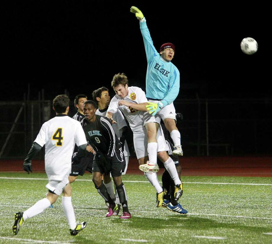 Elsik's goalie, Obed Mena lets the ball get past him over Klein Oak's James Freathy (23) on a free kick almost resulting in the tying goal as Elsik High School held on to beat Klein Oak 2-1 at Butch Theiss Field at Klein Tuesday, Jan. 15, 2013, in Houston. Photo: Johnny Hanson, Houston Chronicle / © 2013  Houston Chronicle