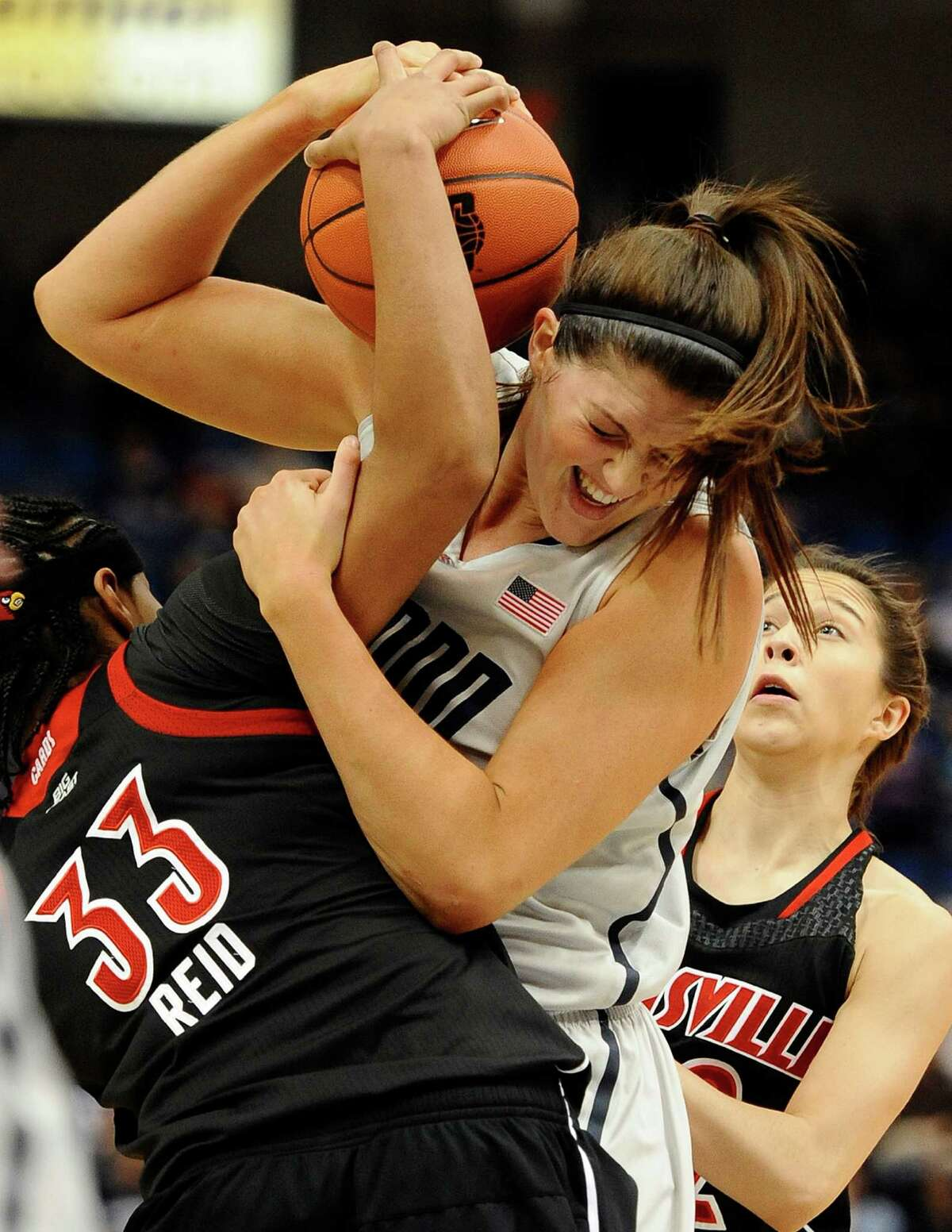 Connecticut's Stefanie Dolson, center battles for control of the ball against Louisville's Monique Reid, left and Louisville's Jude Schimmel, right, during the first half of an NCAA college basketball game in Hartford, Conn., Tuesday, Jan. 15, 2013. (AP Photo/Jessica Hill)