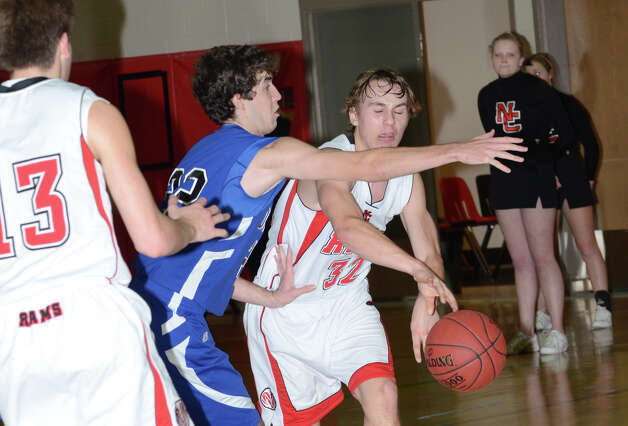 New Canaan's Erik Jager (32) attempts to pass the ball as Darien's Henry Baldwin (22) defends during the boys basketball at New Canaan High School on Tuesday, Jan. 15, 2013. Photo: Amy Mortensen / Connecticut Post Freelance
