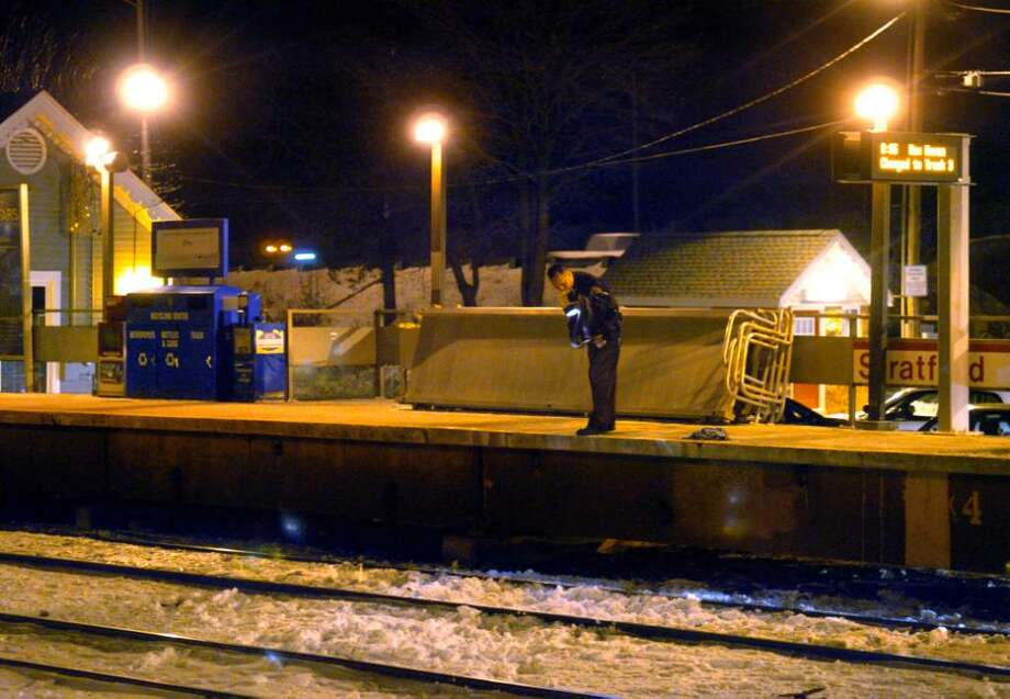 A police officer shines his flashlight on the tracks where a woman was struck by a train Wednesday evening at the Stratford Railroad Station. Photo: Autumn Driscoll / Connecticut Post