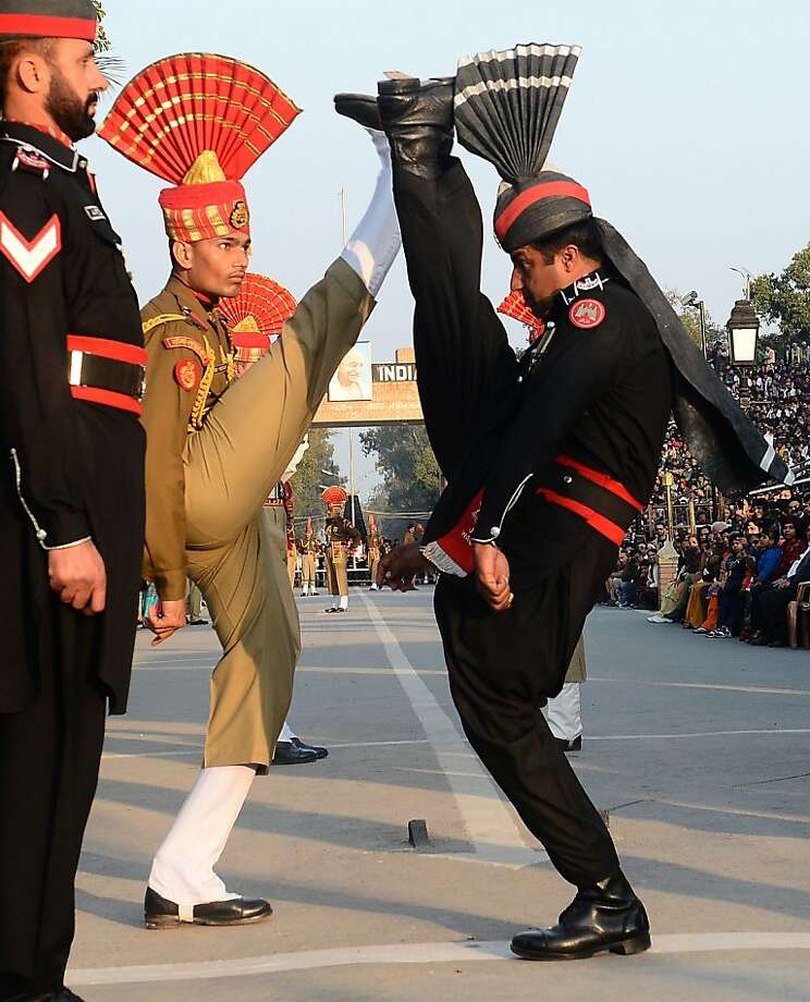 "Pakistani Rangers (in Black) and Indian Border Security Force personnel (in Brown) perform the 'flag off' ceremony at the Pakistan-India Wagah Border Post on January 15, 2013.  Indian Prime Minister Manmohan Singh warned Tuesday that there ""cannot be business as usual"" with neighbouring Pakistan after last week's deadly flare-up along the border in disputed Kashmir. AFP PHOTO/Arif ALIArif Ali/AFP/Getty Images Photo: Arif Ali, AFP/Getty Images"