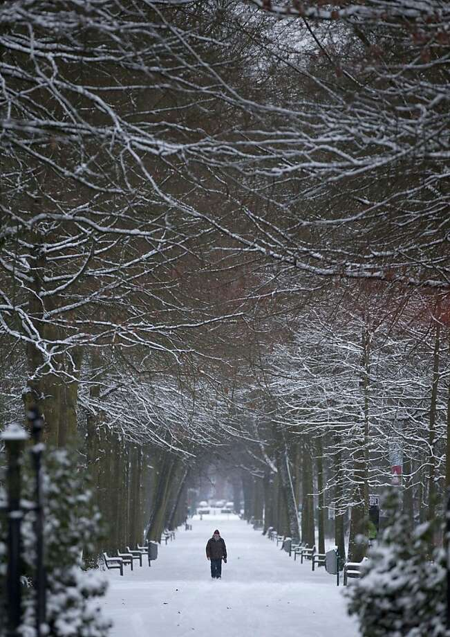 A man walks down a path covered by snow in a public park in Wilrijk, Belgium on Tuesday, Jan. 15, 2013. Belgium experienced the first snow of the season on Tuesday which snarled traffic in early morning rush hour. (AP Photo/Virginia Mayo) Photo: Virginia Mayo, Associated Press