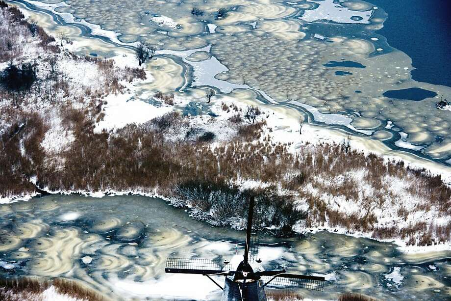 TOPSHOTS  Snow covers the historic windmills at Kinderdijk, The Netherlands, on January 15, 2013. In 1997 the windmills were put on the UNESCO World Heritage List.