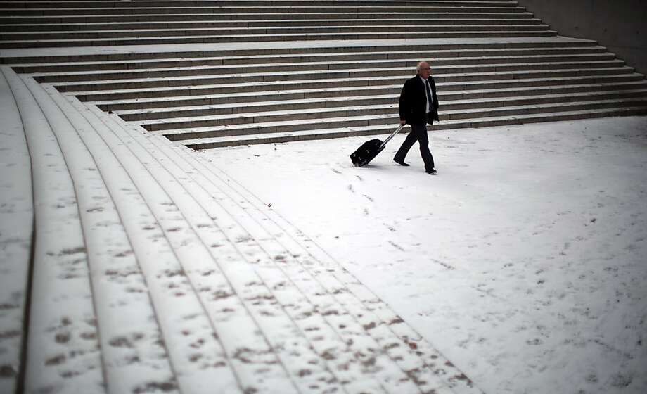 A man walks through the snow in the government district in Berlin,Germany, Tuesday, Jan. 15, 2013. (AP Photo/dpa, Michael Kappeler) Photo: Michael Kappeler, Associated Press