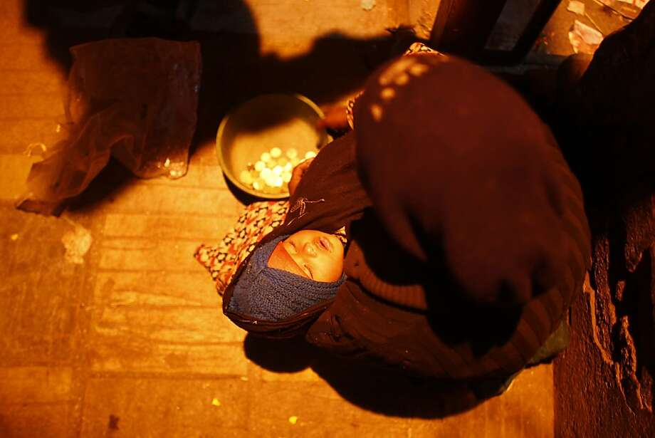 A homeless woman begs as her child sleeps in her arms at the Basantapur Durbar Square in Katmandu, Nepal, Tuesday, Jan. 15, 2013. Basantapur Durbar Square is the plaza in front of the old royal palace and is a place of tourist interest. (AP Photo/Niranjan Shrestha) Photo: Niranjan Shrestha, Associated Press