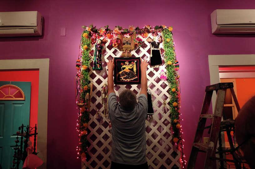 Bernard Sanchez positions a decorative panel on an altar for his family at the Rinconcito de Esperan