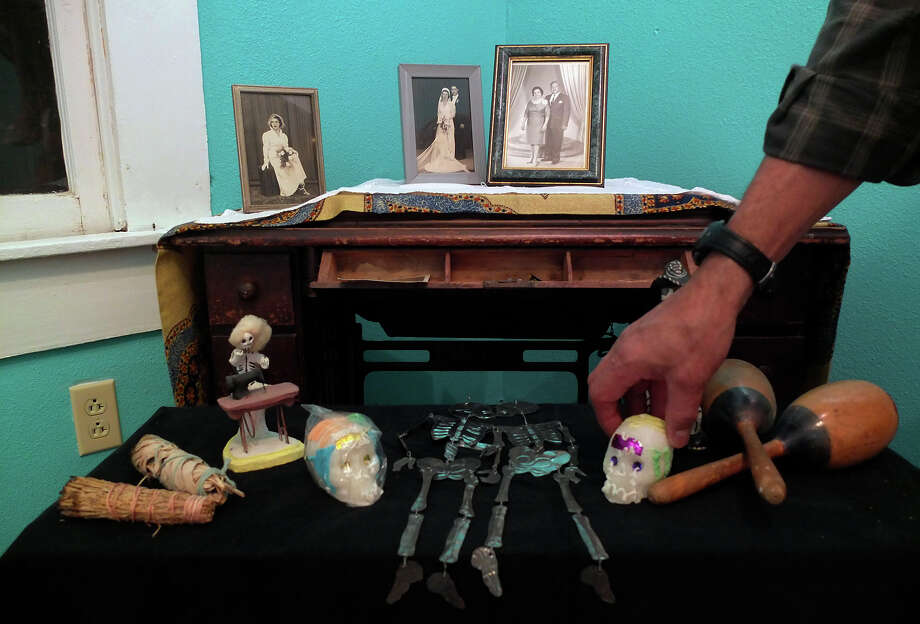 Roland Mazuca places a wax figure of a skull on an altar he's creating to honor his mother and father at the Rinconcito de Esperanza house on Tuesday, Oct. 30, 2012.  Photo: Kin Man Hui, San Antonio Express-News / ©2012 San Antonio Express-News