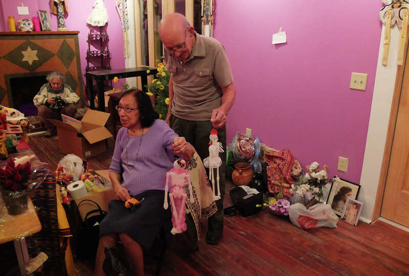 Isabel Sanchez and her husband, Enrique, hold tiny skeletons dolls that she created to place on a fa