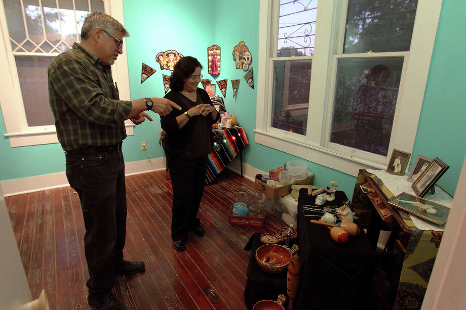 Roland Mazuca (left) talks ideas with Donna Guerra about a Day of the Dead altar he's creating to honor his mother and father at the Rinconcito de Esperanza house on Tuesday, Oct. 30, 2012. About 20 altars were being put in the home which serves as a center for historical preservation for the Westside of San Antonio. A celebration for Dia de Los Muertos will be held at the home on Nov. 1 and will remain on display for 10 days thereafter. Photo: Kin Man Hui, San Antonio Express-News / ©2012 San Antonio Express-News