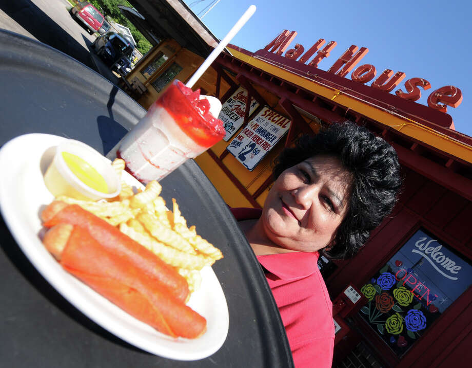 Aimee Delgado shows off the Crispy Dog and Fries from the Malt House at 115 S. Zazamora St. Photo: ROBIN JERSTAD, For The San Antonio Express-News / SAN ANTONIO EXPRESS-NEWS
