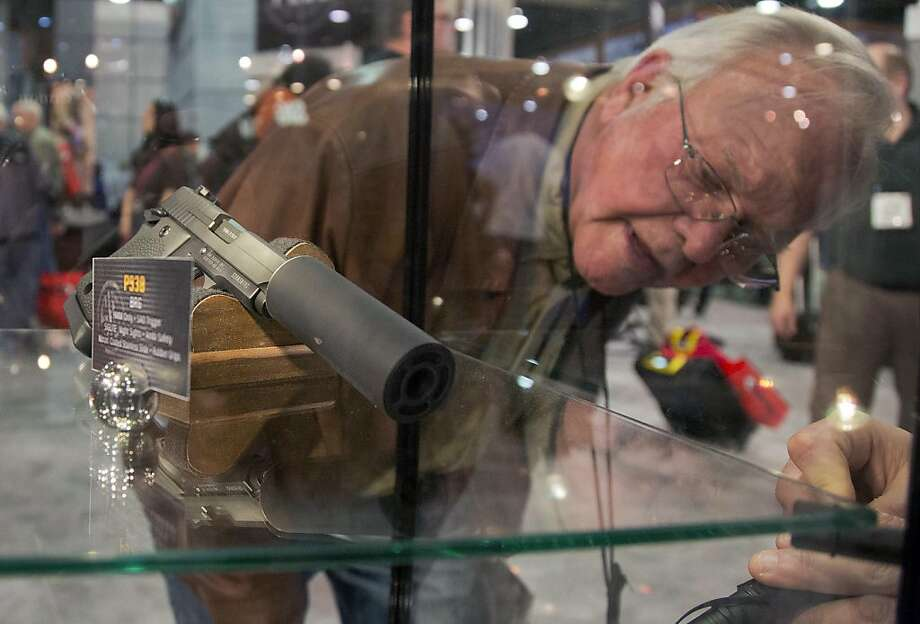 A convention attendee looks through a Sig Sauer display case of various guns including a P938 Nightmare 9mm semiautomatic pistol at the 35th annual SHOT Show, Tuesday, Jan. 15, 2013, in Las Vegas. The National Shooting Sports Foundation was focusing its trade show on products and services new to what it calls a $4.1 billion industry, with a nod to a raging national debate over assault weapons. (AP Photo/Julie Jacobson) Photo: Julie Jacobson, Associated Press