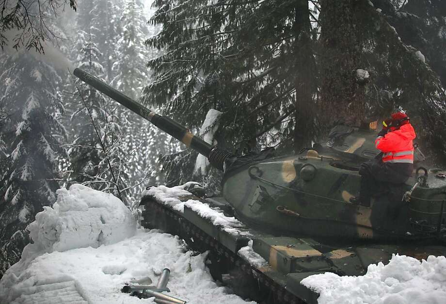 Washington State Department of Transportation avalanche technician Harlan Sheppard sits on the turret of one of two M60 tanks tucked into two locations along US 2 firing artillery shells at a mountainside near the Stevens Pass summit Tuesday, Jan. 8, 2013. Usually the work is done late at night or very early in the morning, temporarily closing US 2 while avalanches are triggered. On Tuesday, WSDOT decided they needed to take action in the afternoon because of high avalanche risk. (AP Photo/The Daily Herald, Mark Mulligan) Photo: Mark Mulligan, Associated Press