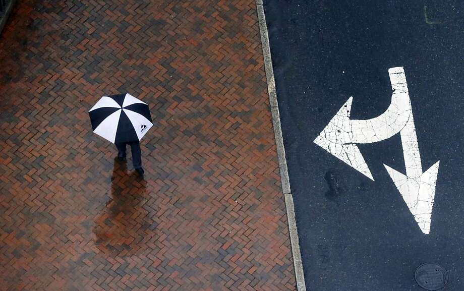 A pedestrian walks north on 9th Street near the State Capitol in Richmond, Va., on Monday, Jan. 14, 2013, as rain moved into the metro area. (AP Photo/Richmond Times-Dispatch, Bob Brown) Photo: Bob Brown, Associated Press