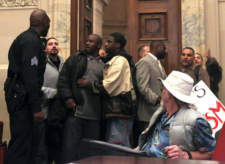 "An Oakland Police officer talks with a group of men that got into a verbal exchange with hecklers in the gallery opposed to the ""stop and frisk"" policy. The Oakland City Council's Public Safety Committee meeting Tuesday heard from hundreds of citizens that wanted to voice their opinions about consultant William Bratton, ""stop and frisk "" policy Tuesday Jan 15, 2013, in Oakland California. Photo: Lance Iversen, The Chronicle"