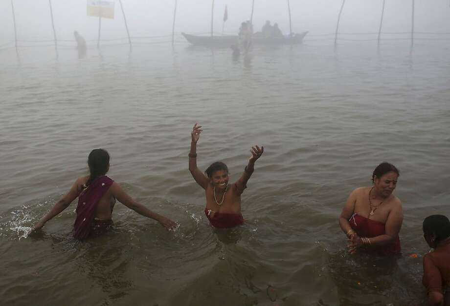 Indian Hindu devotees bathe at Sangam, the confluence of the holy rivers Ganges and Yamuna and mythical Saraswati at the Maha Kumbh Mela in Allahabad, India, Tuesday, Jan. 15, 2013. Millions of Hindu pilgrims are expected to take part in the large religious congregation that lasts more than 50 days on the banks of Sangam during the Maha Kumbh Mela in January 2013, which falls every 12th year. (AP Photo/Kevin Frayer) Photo: Kevin Frayer, Associated Press