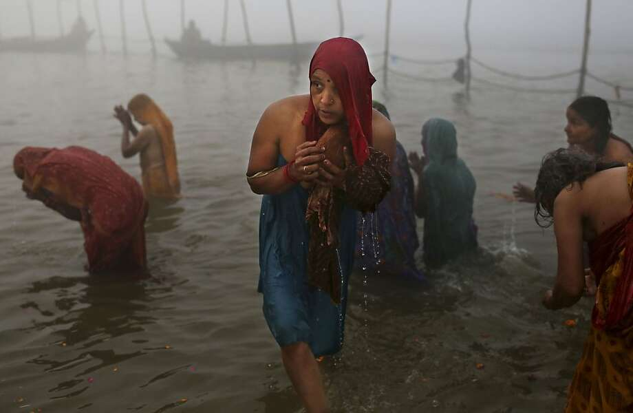 An Indian Hindu woman carries a coconut as she takes part in morning prayers while bathing at Sangam, the confluence of the holy rivers Ganges and Yamuna and mythical Saraswati during the Maha Kumbh Mela in Allahabad, India, Tuesday, Jan. 15, 2013. Millions of Hindu pilgrims came to take part in the world largest religious congregation that lasts more than 50 days. The congregation falls once every 12 year. (AP Photo/Kevin Frayer) Photo: Kevin Frayer, Associated Press