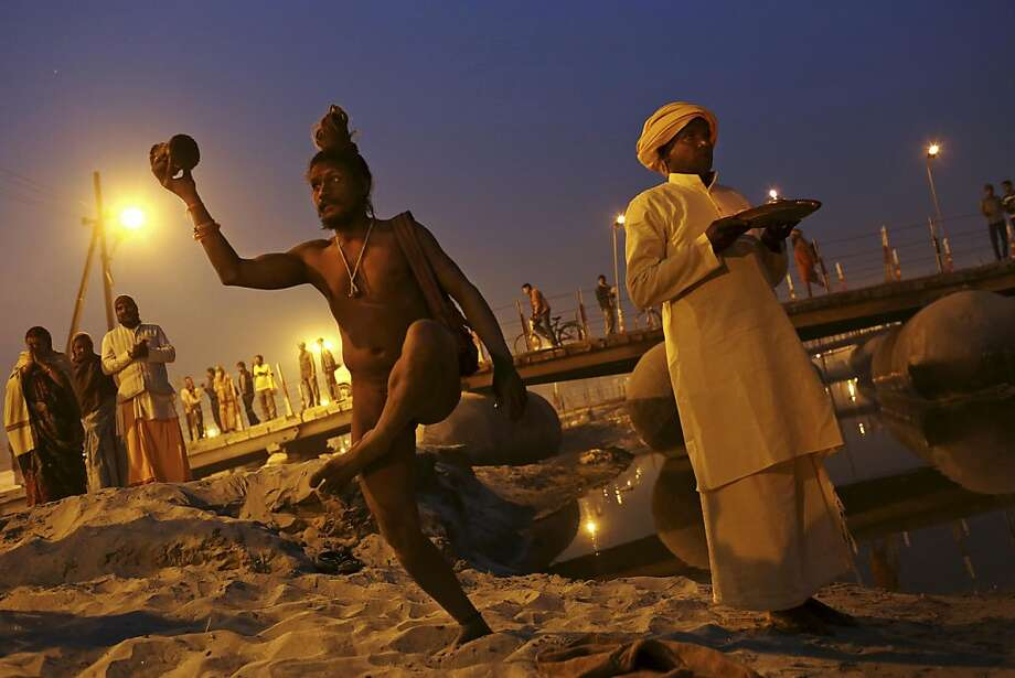 An Indian Hindu holy man, or Naga Sadhu, stands naked next to a priest during an evening prayer ceremony known as Arti at Sangam, the confluence of the holy rivers Ganges and Yamuna and mythical Saraswati at the Maha Kumbh Mela in Allahabad, India, Tuesday, Jan. 15, 2013. Millions of Hindu pilgrims are expected to take part in the large religious congregation that lasts more than 50 days on the banks of Sangam during the Maha Kumbh Mela in January 2013, which falls every 12th year. (AP Photo/Kevin Frayer) Photo: Kevin Frayer, Associated Press
