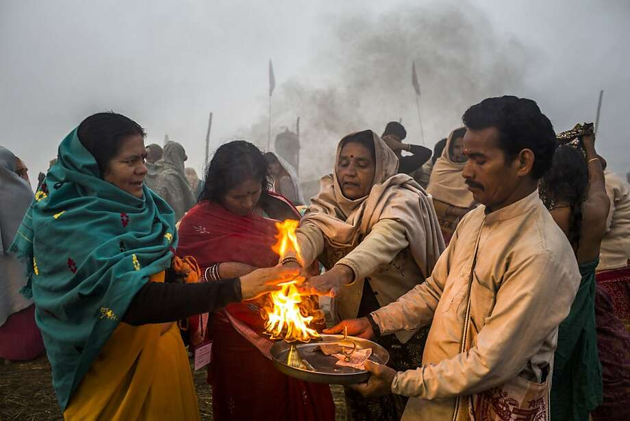 ALLAHABAD, INDIA - JANUARY 15: Hindu devotees perform an aarti or Hindu ceremony on the banks of Sangam, the confluence of the waters of the holy rivers Ganges, Yamuna and the mythical Saraswati, during the Maha Kumbh Mela on January 15, 2013 in Allahabad, India. The Maha Kumbh Mela, believed to be the largest religious gathering on earth is held every 12 years on the banks of Sangam, the confluence of the holy rivers Ganga, Yamuna and the mythical Saraswati. The Kumbh Mela alternates between the cities of Nasik, Allahabad, Ujjain and Haridwar every three years. The Maha Kumbh Mela celebrated at the holy site of Sangam in Allahabad, is the largest and holiest, celebrated over 55 days, it is expected to attract over 100 million people. (Photo by Daniel Berehulak/Getty Images) Photo: Daniel Berehulak, Getty Images