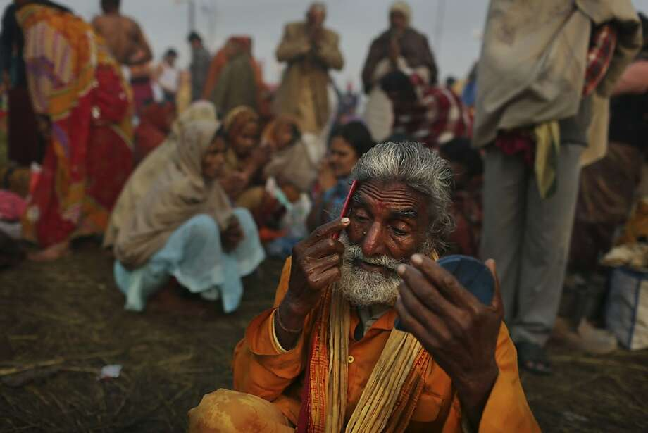 An Indian Hindu holy man combs his eyebrows after taking a bath at Sangam, the confluence of the holy rivers Ganges, Yamuna, and mythical Saraswati during the Maha Kumbh Mela in Allahabad, India, Tuesday, Jan. 15, 2013. Millions of Hindu pilgrims came to take part in the world largest religious congregation that lasts more than 50 days. The congregation falls once every 12 year. (AP Photo/Kevin Frayer) Photo: Kevin Frayer, Associated Press